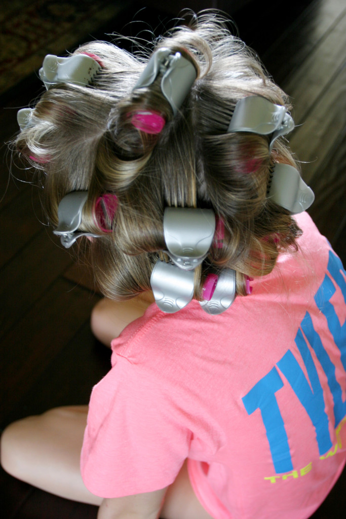 Looking down at a girl sitting cross-legged on the floor wearing a pink and blue tshirt with hot pink and silver rollers in her hair.
