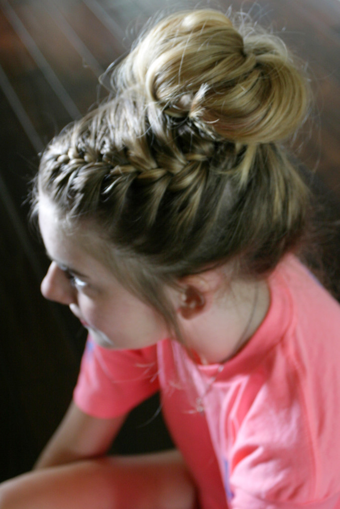 Side view of a girl with blonde hair showing off a side braid and voluminous messy bun.