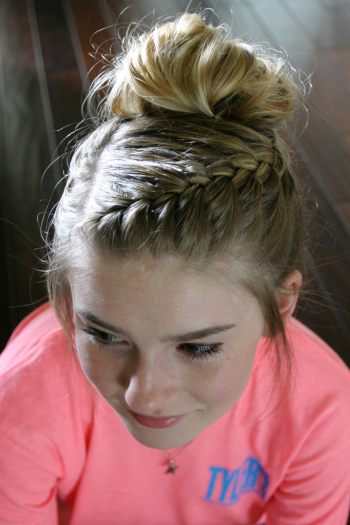 Front angle of a girl with an intricate side braid that ends in a blonde messy bun piled atop her head.