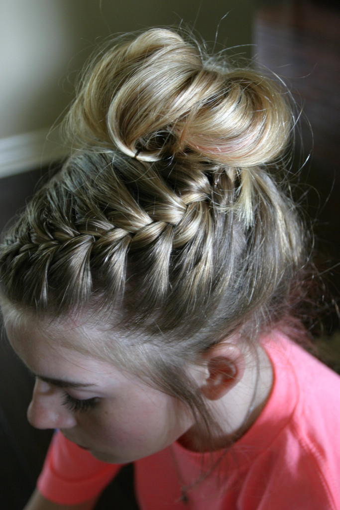 Top left-side angle of a girl's head with intricate braid that ends in a bun on the top of her head.
