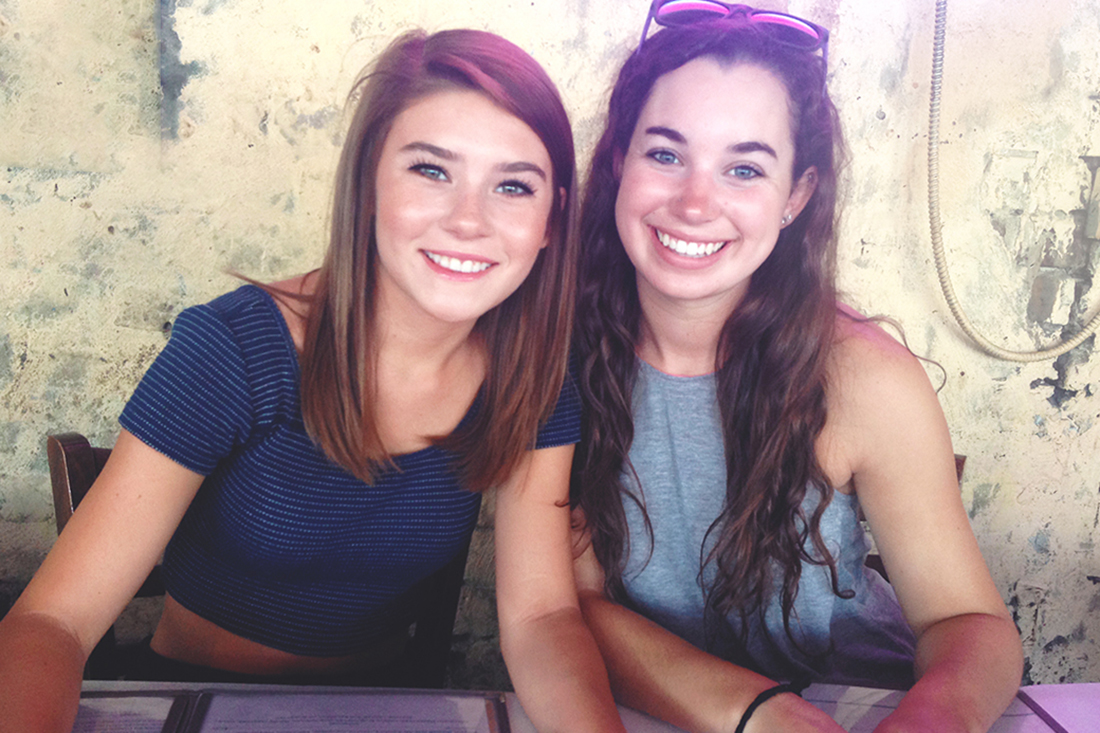 Two young, smiling brunette girls awaiting lunch at Hueys on River Street in Savannah GA.