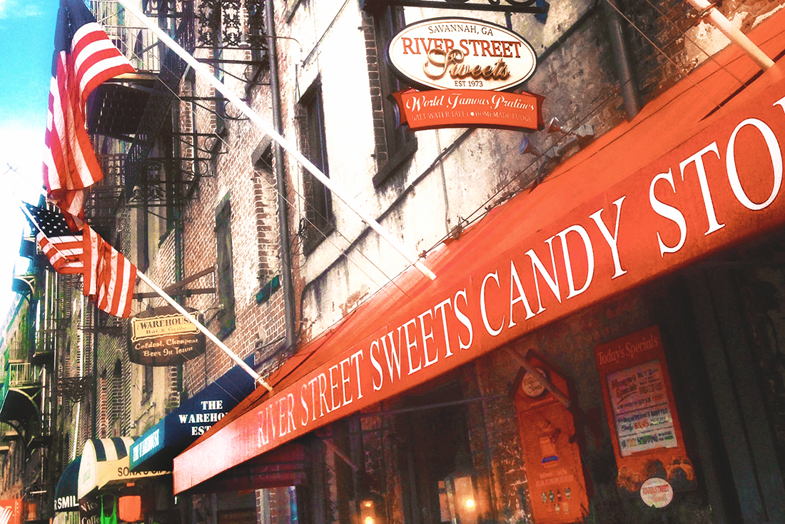 On River Street in Savannah, a storefront is lined with colorful flags and a bright red awning with white lettering that reads River Street Sweets Candy Store.