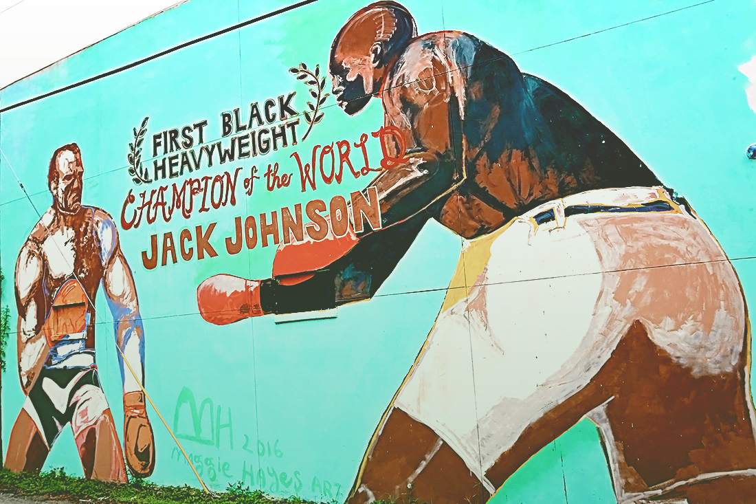 Two-story wall painted with Jack Johnson The First Black Heavyweight Champion of the World sparring with another man.