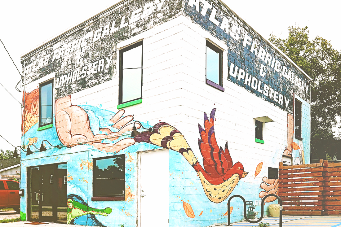 A colorful mural of showing a bird and nature scenes wraps three sides of a yoga studio in Savannah.