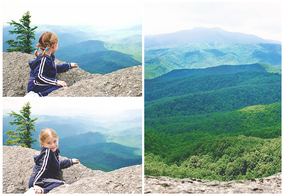 A young girl looking over the edge of a rock at a beautiful rolling green and blue mountainous vista.