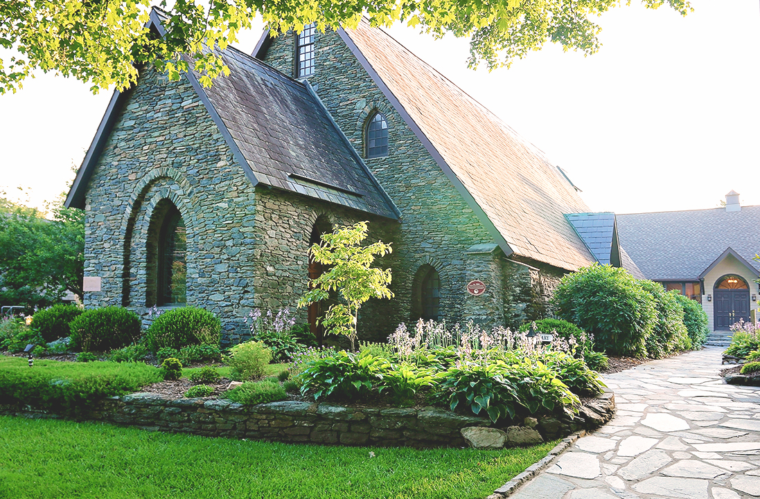 Things to do in Blowing Rock NC: Image of church exterior with beautiful landscaping at sunset during the springtime.