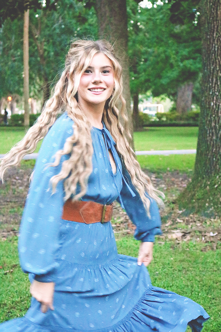 Mamma Mia Hair Tutorial: Image of a young girl smiling and twirling in a long, blue peasant dress