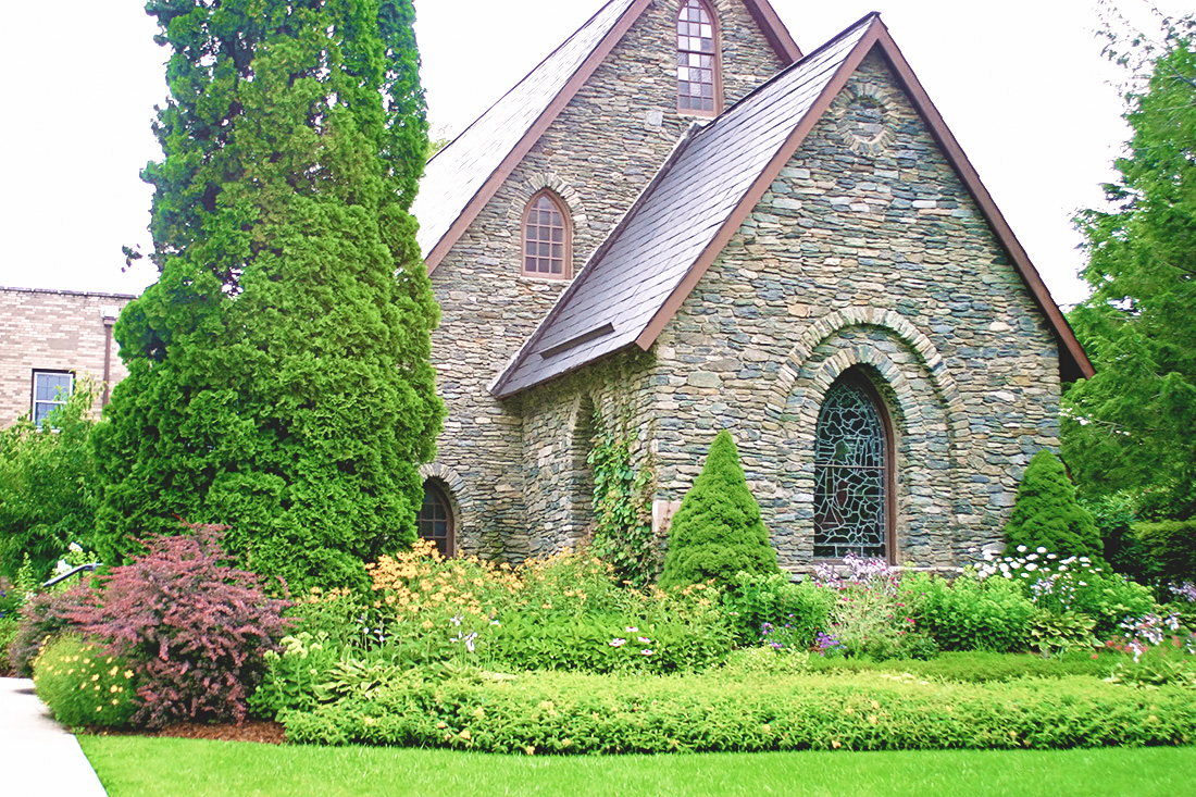 Things To Do in Blowing Rock NC: Image of the exterior of Rumple Memorial Church in late summer when all the plants are fully grown.