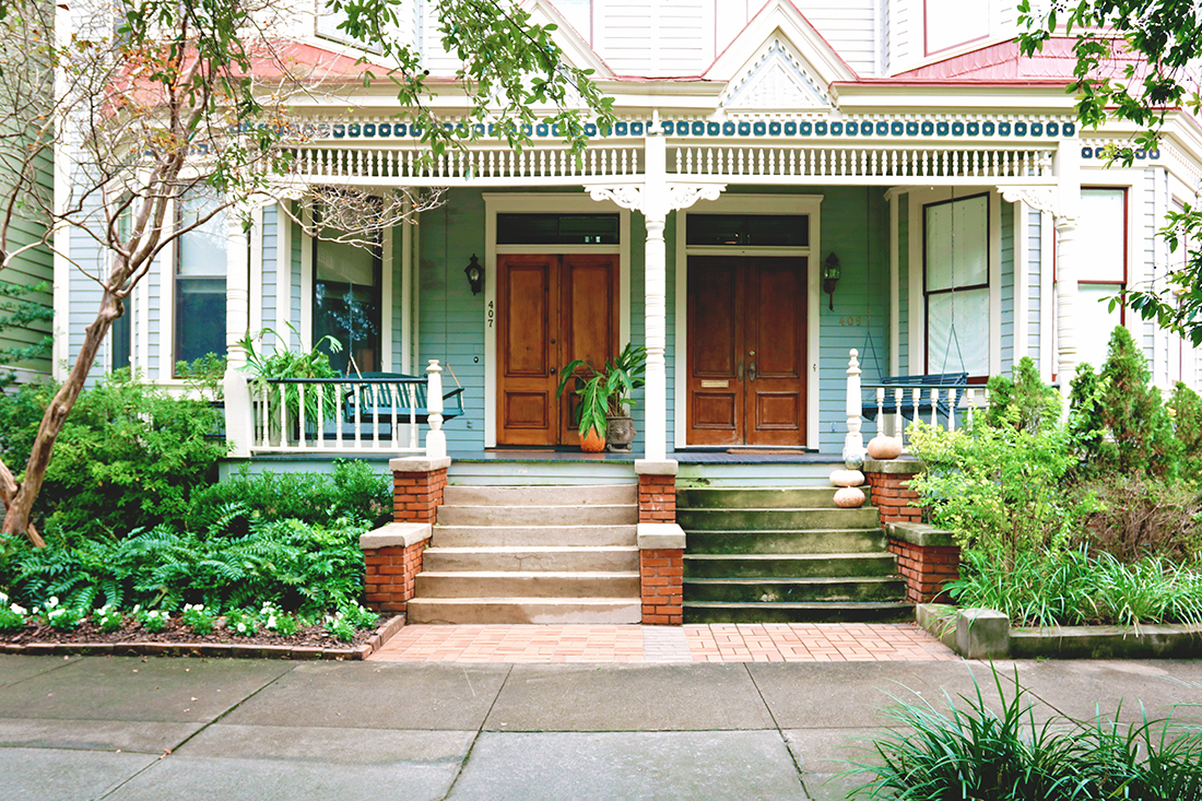 Two nearly identical front porch entryways on a multi-family Victorian-style home. The home is painted blue and has a decorative navy and cream-colored trim. The entry on the right side shows slight signs of aging in its moss-covered stairs.