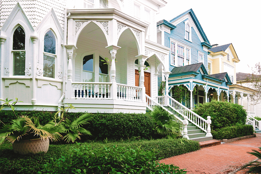 A row of three ornately-detailed 3-story Victorian homes painted, from left to right, with white, blue, and yellow.