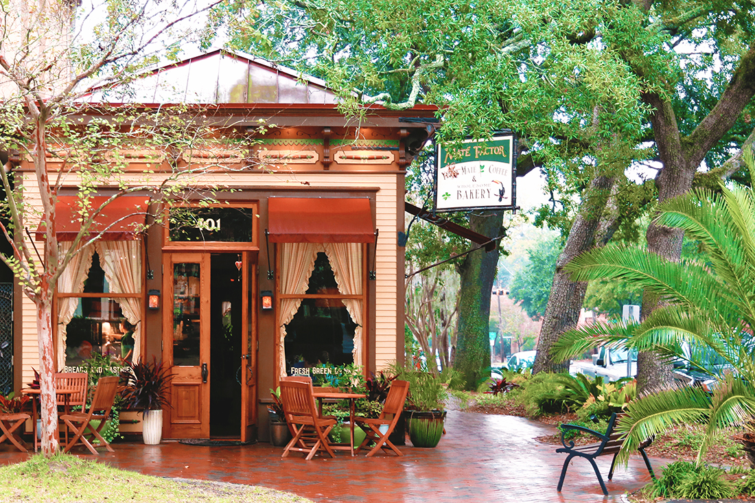Tiny yelllow-painted bakery on a rain-soaked street shaded by large oak trees.
