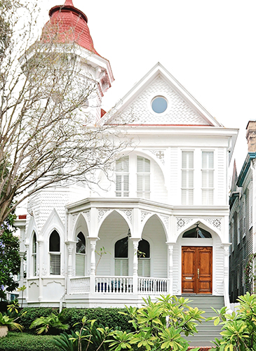 Three-story white Victorian home with an arched porch trim and a turreted roofline.