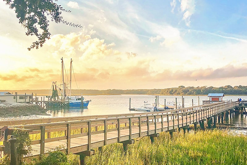 Hilton Head Island's Dockside Restaurant's long wooden pier with shrimp boats and a beautiful yellow sunset in the background.