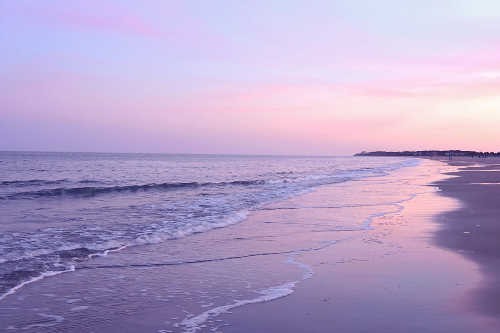 Hilton Head sunset beach scene with pinkish-purple tinted skies on Folly Beach.