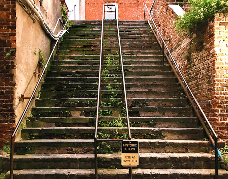 The Stone Stairs of Death in Savannah are steep and old, with crumbling bricks and moss-covered areas.
