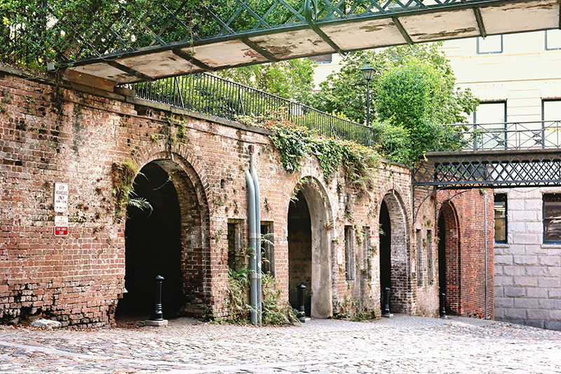 Cobblestone streets meet a brick wall with 4 tunnel-like openings at the Cluskey Vaults.