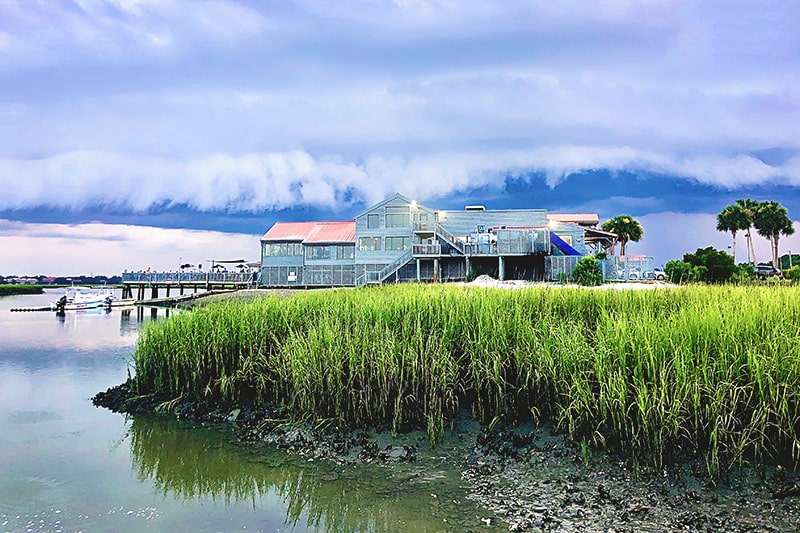 Wide shot of The Old Oyster Factory on Hilton Head Island as a massive wave-shaped storm cloud looms overhead.