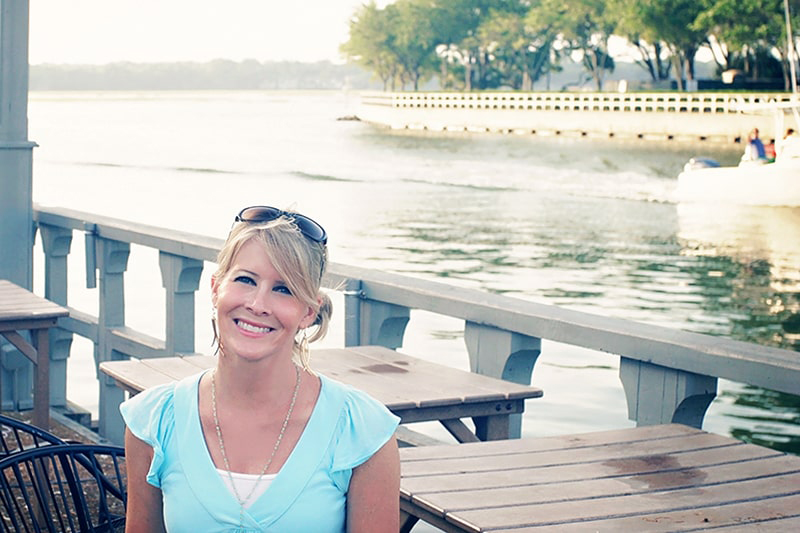 Girl in a short sleeved turquoise blue top smiling as a boat enters the marina behind her.