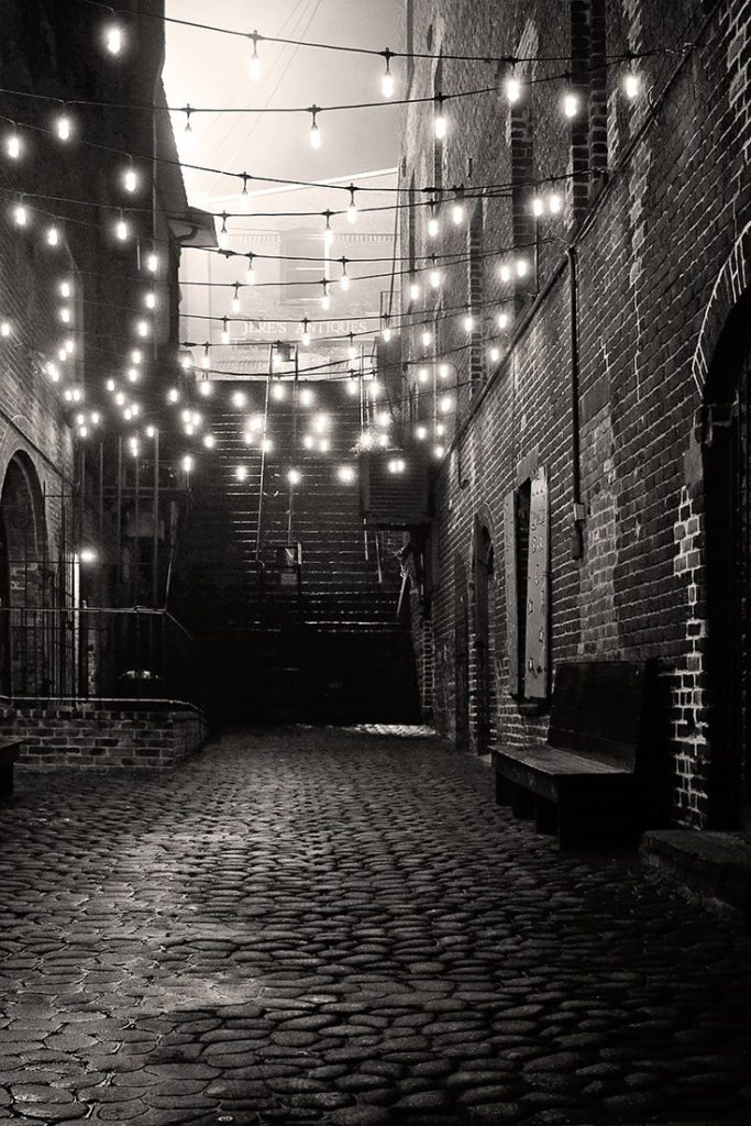 B&W dimly lit alleyway leading to the Stone Stairs of Death in Savannah GA.